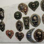 Wiszące na ścianie metalowe maski wykonane przez osadzonych w Zakładzie Karnym w Tarnowie-Mościcach