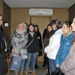 Grupa studentów z opiekunem stojąca w sali widzeń Zakładu Karnego