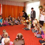 Dzieci siedzą na dywanie w sali zabaw, wśród nich stoją kanclerz, wicekanclerz i dyrektor przedszkola