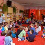 Dzieci siedzące na dywanie w sali zabaw