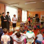 Kanclerz, wicekanclerz i dyrektor przedszkola wśród siedzących na dywanie dzieci w sali zabaw