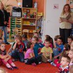 Przedszkolaki siedzą na dywanie, wychowawczyni stojąc czyta książkę