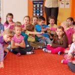Dzieci siedzą na dywanie w sali zabaw