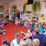 """Dzieci siedzą na dywanie, wśród nich stoją wychowawczyni oraz studentka Gertruda Gałek z koła naukowego """"Paidagogos"""""""