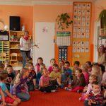 """Prezes koła """"Paidagogos"""" Marta Falińska wśród siedzących na dywanie dzieci w sali zabaw"""