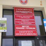 Tablica informacyjna przed wejściem do budynku uniwersytetu