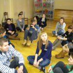 Studenci siedzący na podłodze w sali ćwiczeń