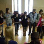 Studenci podczas zajęć tanecznych trzymają się za ręce skrzyżowane za plecami