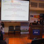 Wystąpienie prelegenta, na pierwszym planie ekran z prezentacją multimedialnąje - przemówienie zaproszonych gości