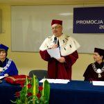 Rektor prof. Michał Woźniak z mikrofonem, obok przy stole prezydialnym siedzą dziekan dr Jolanta Stanienda i kanclerz mgr Zofia Kozioł