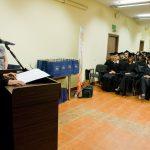 Wyróznieni absolwenci w togach, na mównicy stoi dziekan dr Jolanta Stanienda