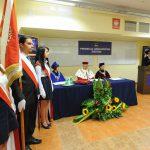 Poczet sztandarowy, w tle władze uczelni za stołem prezydialnym
