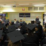 Studenci w Absolwenci uczestniczący w promocji ubrani w czarne togi i birety
