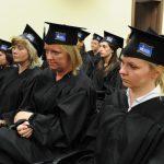 Absolwenci uczestniczący w promocji ubrani w czarne togi i birety
