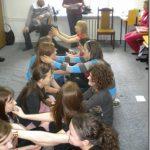 Uczestnicy wykonują ćwiczenie siedząc na podłodze parami naprzeciw siebie