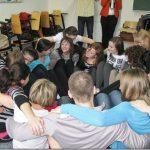 Studenci podczas ćwiczenia siedzą na podłodze w kole, obejmują się ramionami
