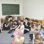 Uczestnicy siedzą na podłodze parami i wykonują ćwiczenie
