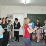 Studenci stoją kołem w sali, na środku dziewczyna z zasłąniętymi przepaską oczyma