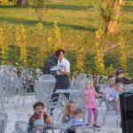 Studentka z tacą pomiędzy stolikami postawionymi przed hotelową restauracją