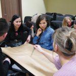 Grupa uczestników wykonujących wspólnie prace plastyczną