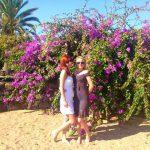 Dwie studentki w ogrodzie na tle różowo kwitnącego krzewu