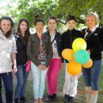 Studentki z uczestnikami majówki w ogrodzie przedszkola, jedna z osób trzyma żółto zielone balony