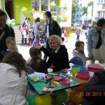 Studentki podczas malowania twarzy dzieciom, w tle rodzice z dziećmi