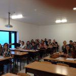 Studenci siedzący przy stolikach w sali wykładowej podczas lektoratu języka portugalskiego