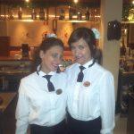 Studentka i jej współpracowniczka na tle zaplecza hotelowego baru