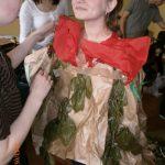 Studentka ubierama przez koleżankę w ekologiczny strój z papieru pakowego, bibuły i gałązek