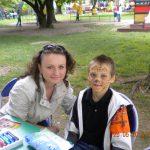Studentka i chłopiec siedzący przy stoliku w ogrodzie. Chłopiec ma wymalowaną twarz