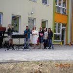 """Dyrektor przedszkola nr 34 wraz z trzema studentkami z koła """"Paidagogos"""" przed budynkiem przedszkola, obok zespół muzyczny"""