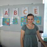 Studentka przed tablicą lekcyjną na której umieszczono nazwy witamin i zawierające je owoce oraz warzywa