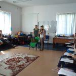 Sala ćwiczeniowa - na środku stojące trzy studentki jedna z nich ma zasłonięte oczy i trzyma w ręku jabłko