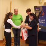Kanclerz, wicekanclerz i przewodniczący jury wręczają nagrodę uczestniczce