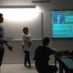 Troje studentów w sali wykładowej podczas prezentacji multimedialnej na zajęciach z nowoczesnych technologii