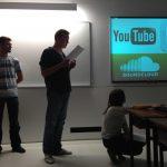 Sala lekcyjna - troje studentów. Jeden z nich odczytuje z kartki tekst, komentując wyświetlaną na tablicy prezentację mulimedialną
