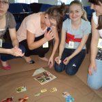 Cztery studentki klęczą na podłodze przygotowując projekt o zdrowej i niezdrowej żywności