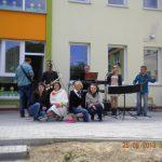 """Dyrektor przedszkola nr 34 wraz z trzema studentkami z koła """"Paidagogos"""" przed budynkiem przedszkola, za nimi pięcioosobowy zespół muzyczny"""