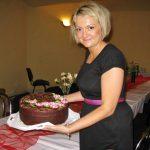 Prezes koła Marta Falińska prezentuje domowy tort ozdobiony różowymi stokrotkami