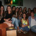 Grupa studentów turystyki siedząca w klubie podczas wieczoru karaoke