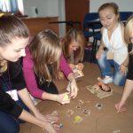 Pięć studentek klęczy na podłodze przygotowując projekt o zdrowej i niezdrowej żywności