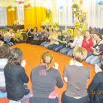 Uczestnicy zajęć logorytmicznych siedzący na podłodze na piętach
