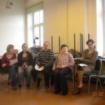 Grupa pięciu studentów siedzącycj w sali lekcyjnej