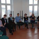 Kanclerz i wicekanclerz uczelni oraz troje innych uczestników zajęć siedzących na krzesłach podczas zajęć