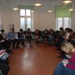 Uczestnicy siedzą na krzesłach ustawionych w kole i czyteją rozdany przez prowadzącego tekst