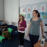 Dwie studentki stoją przed tablicą na której pogrupowano owoce i warzywa zawierające witaminy A, B, C, E