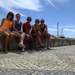 Czworo studentów MWSE siedzących na betonowym obmurowaniu nabrzeża