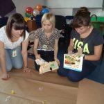 Trzy studentki klęczą na podłodze przygotowując projekt o zdrowej i niezdrowej żywności