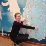 Mgr Anna Karaś kucając pokazuje odległość na wiszącej na ścianie mapie